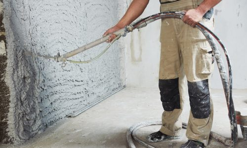 Worker plastering the interior wall with an automatic spraying plaster pump machine