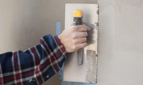 man with a spatula skimming wall